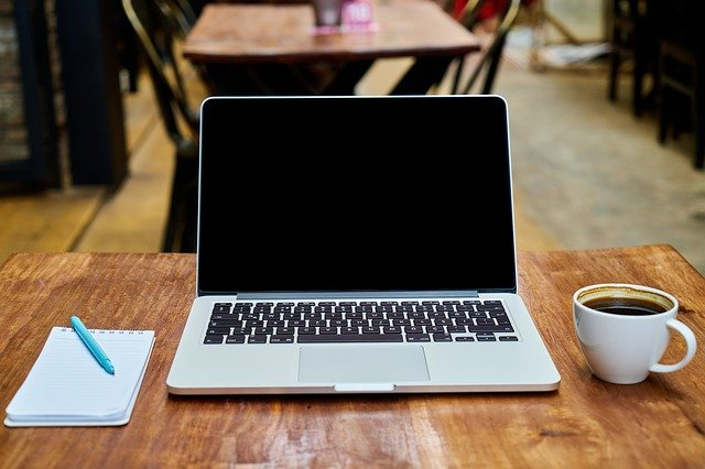 Laptop, cup of coffee and notepad